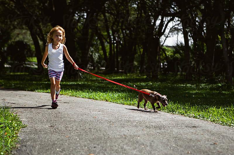 Little Girl Walking a Dog by Stephen Morris for Stocksy United