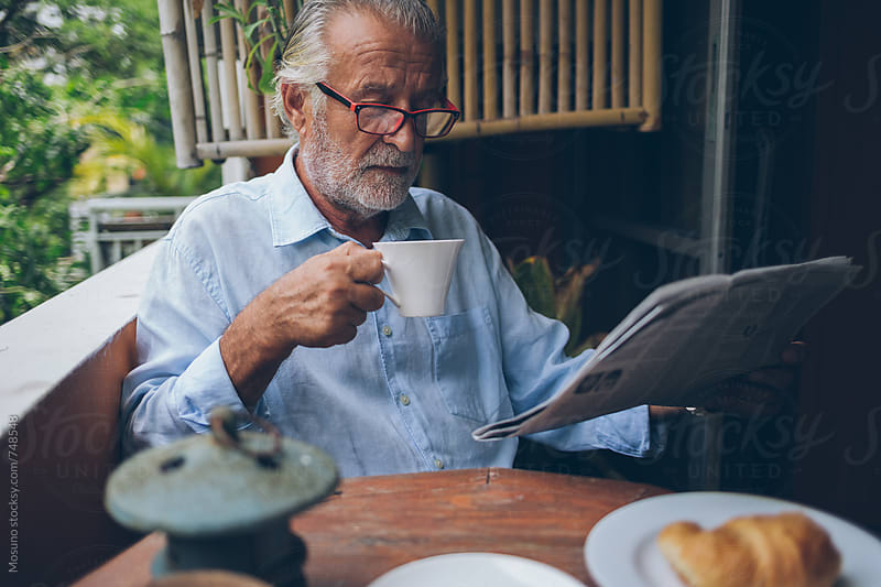 Senior Man Drinking Coffee and Reading Newspaper by Mosuno for Stocksy United