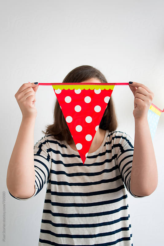 Young woman hiding her face behind bunting by Pixel Stories for Stocksy United
