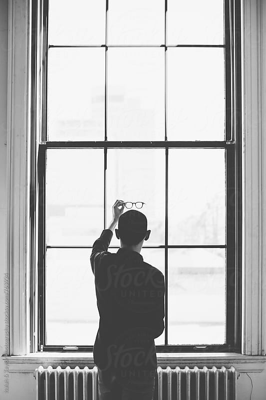 Man holding glasses up by window by Isaiah & Taylor Photography for Stocksy United