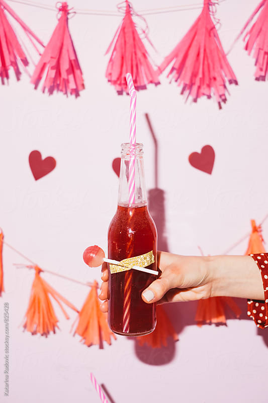 Female Hand Holding Red Juice Bottle at the Party by Katarina Radovic for Stocksy United