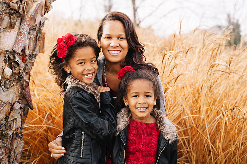 outdoor holiday portrait of a mother and daughters  by Kelly Knox for Stocksy United