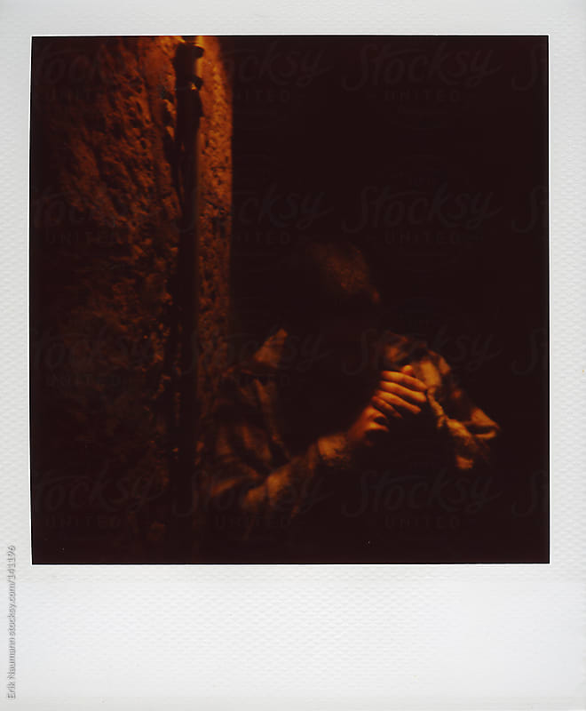 A man lights his cigarette at night by Erik Naumann for Stocksy United
