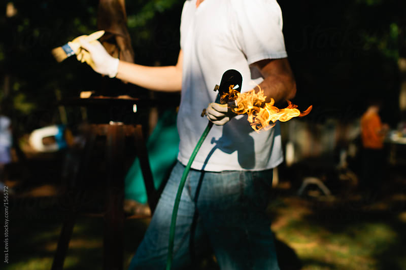 man holding blow torch and paintbrush by Jess Lewis for Stocksy United