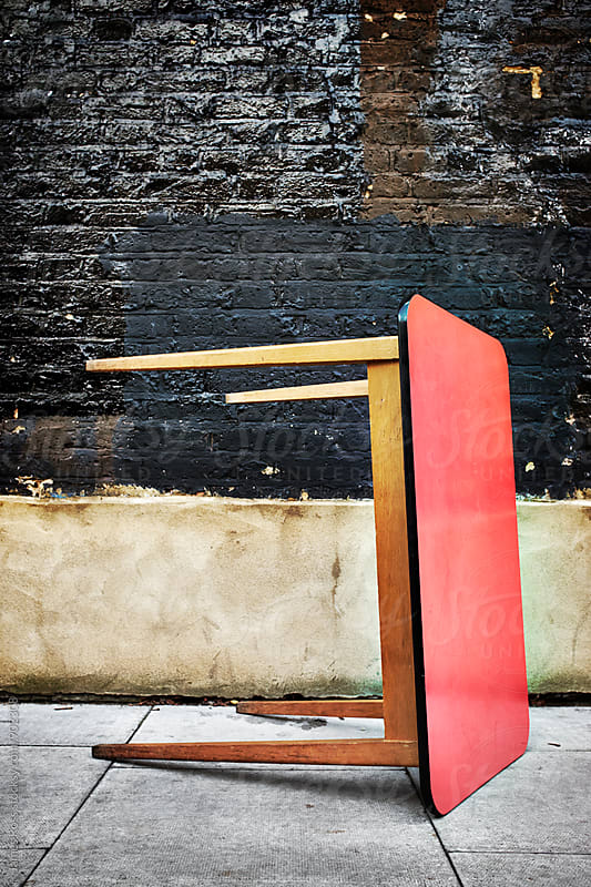 A red kitchen table on the pavement by James Ross for Stocksy United