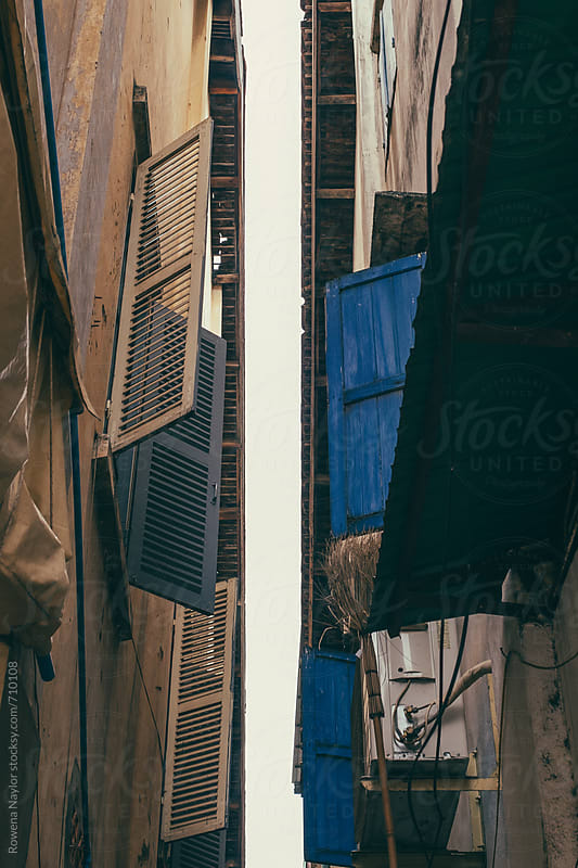 Looking up betwwen buildings in narrow laneway, Cambodia by Rowena Naylor for Stocksy United