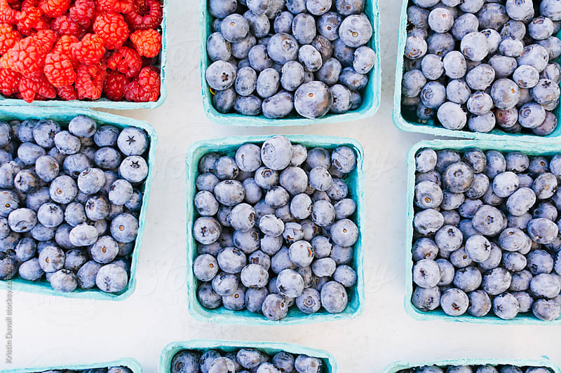 Pints filled with fresh whole blueberries and raspberries at market by Kristin Duvall for Stocksy United