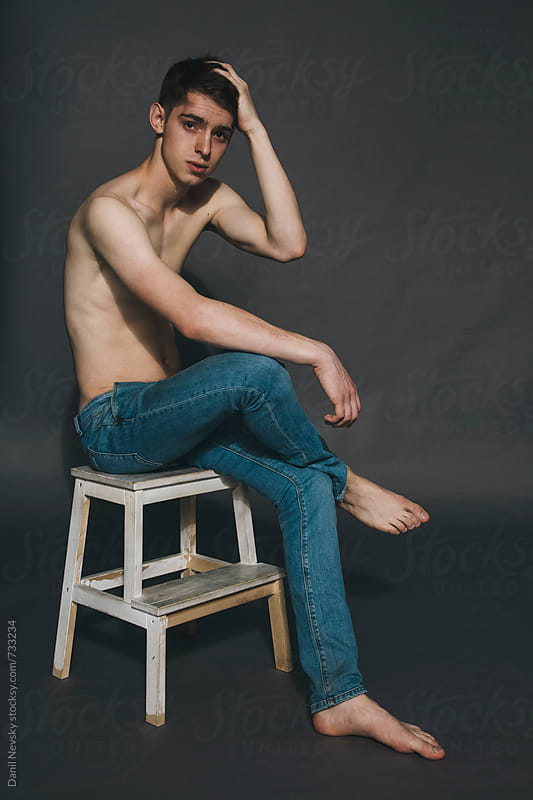 Naked guy sitting on stepladder in the studio by Danil Nevsky for Stocksy United