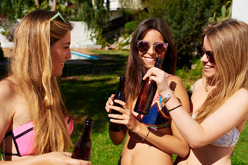 Smiling girlfriends with beer on backyard by Guille Faingold for Stocksy United