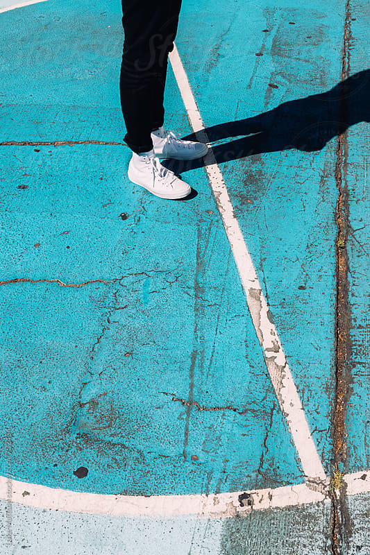 Man Wearing White High Top Converse Standing On Blue Basketball Court by Luke Mattson for Stocksy United