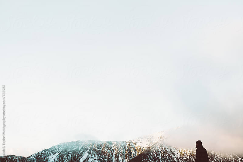 Man with snowy mountains by Isaiah & Taylor Photography for Stocksy United