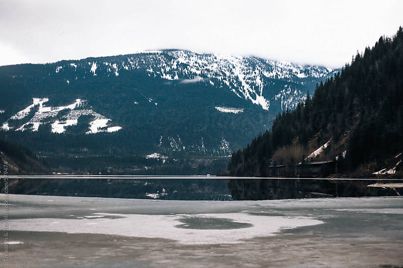 Frozen lake and mountains in the winter by Treasures & Travels for Stocksy United