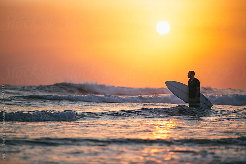 Surfer silhouette in wavy sea at sunset