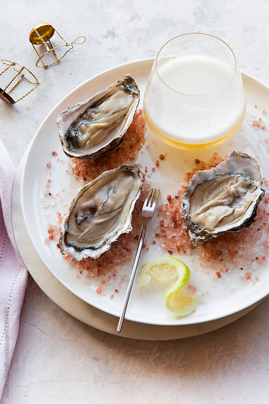 Champagne and  oysters with himalayan crystal salt by Nadine Greeff for Stocksy United