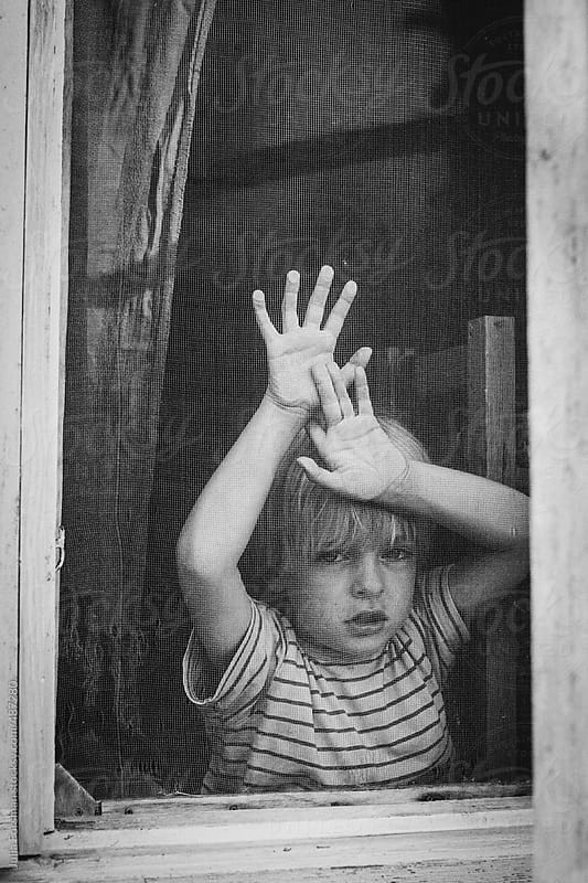 Boy looks out of an old wooden window. by Julia Forsman for Stocksy United
