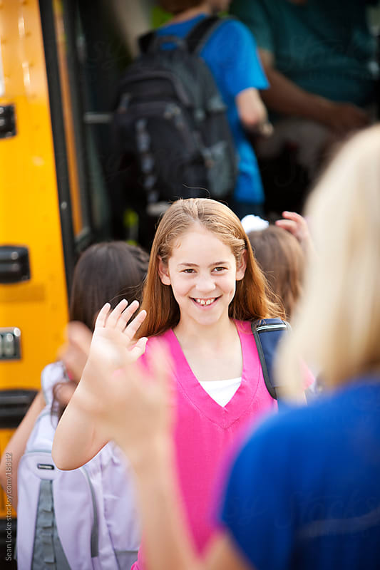 School Bus: Schoolgirl Waves Goodbye by Sean Locke for Stocksy United