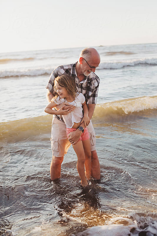 Fun, energetic grandpa playing in waves with young grandchild - girl - on beach at sunset by Rob and Julia Campbell for Stocksy United