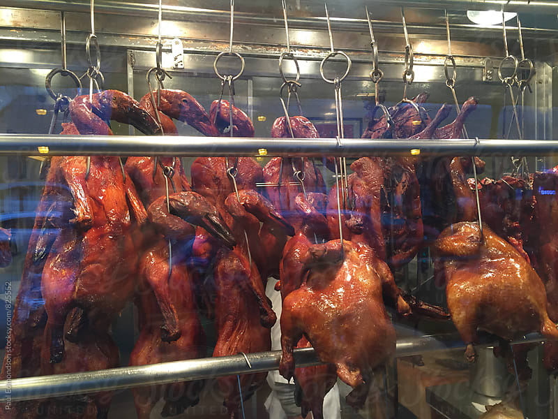 Whole roasted duck hanging in window of Chinatown restaurant  by Paul Edmondson for Stocksy United