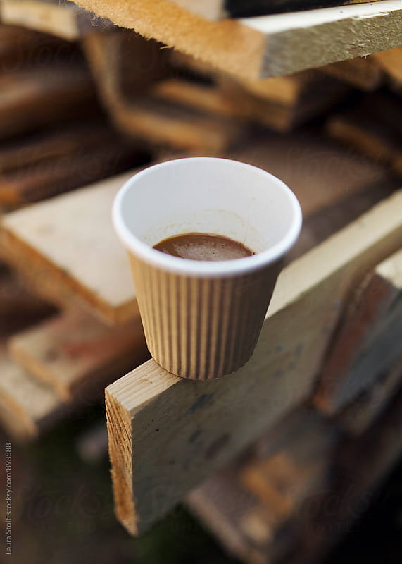 Close up of coffee cup on wooden board on working site by Laura Stolfi for Stocksy United