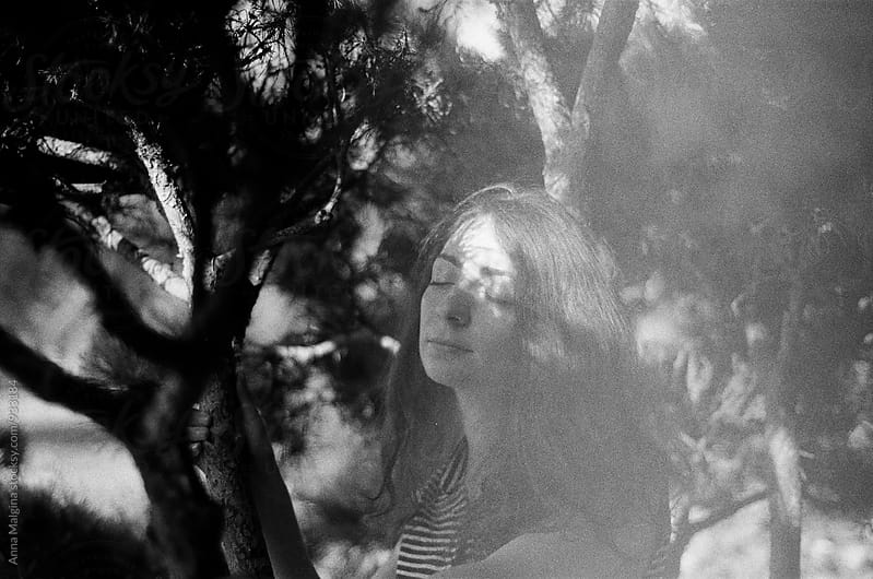 A black and white portrait of a young beautiful woman standing at the shadow of a tree by Anna Malgina for Stocksy United