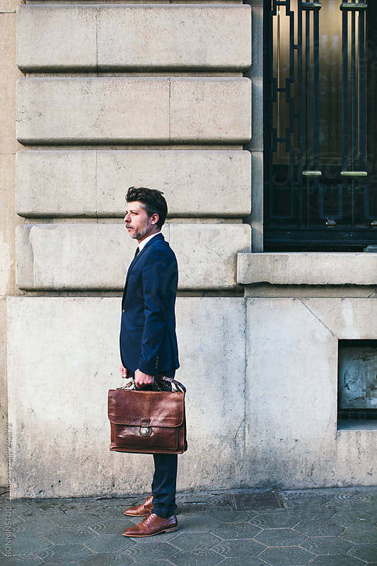 Side view of a mature businessman holding a briefcase in the city. by BONNINSTUDIO for Stocksy United