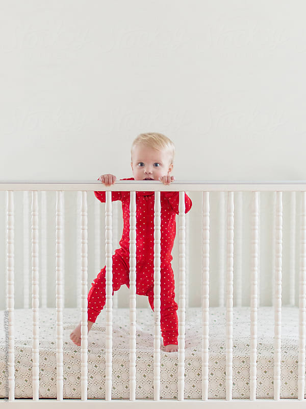 baby standing in her crib in red pajamas by Meaghan Curry for Stocksy United