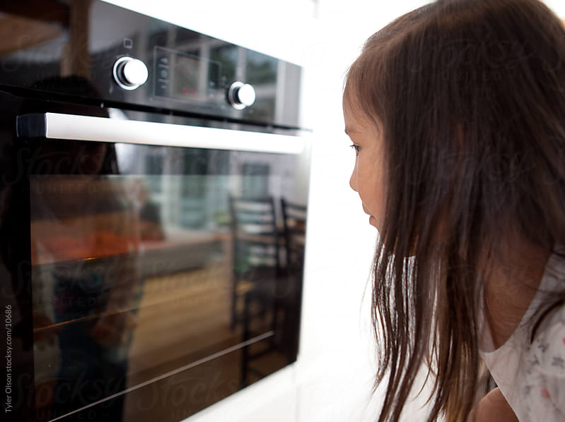 Child Watching Cookies in Oven by Tyler Olson for Stocksy United