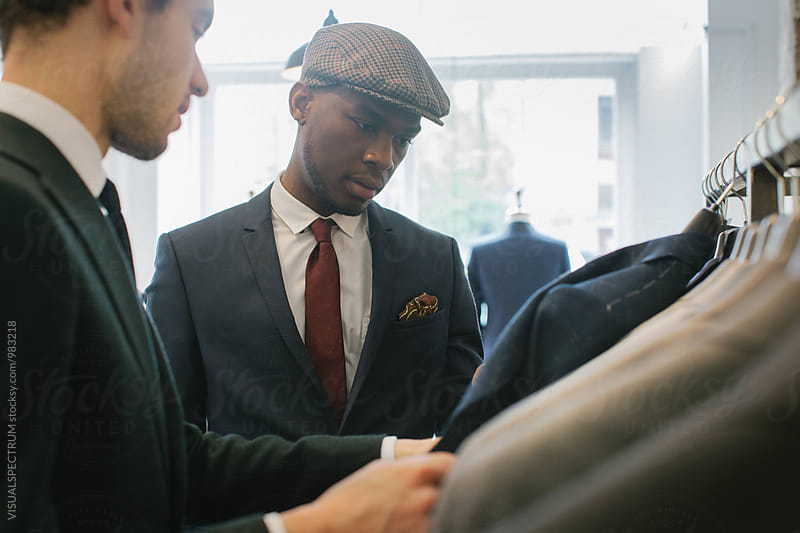 Men's Fashion Shopping - Caucasian Shop Assistant Showing Suits to Young Black Customer by VISUALSPECTRUM for Stocksy United