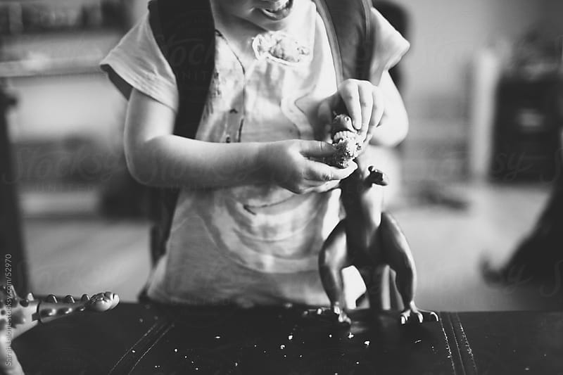 A little boy feeding banana bread to his toy dinosaur by Sarah Lalone for Stocksy United