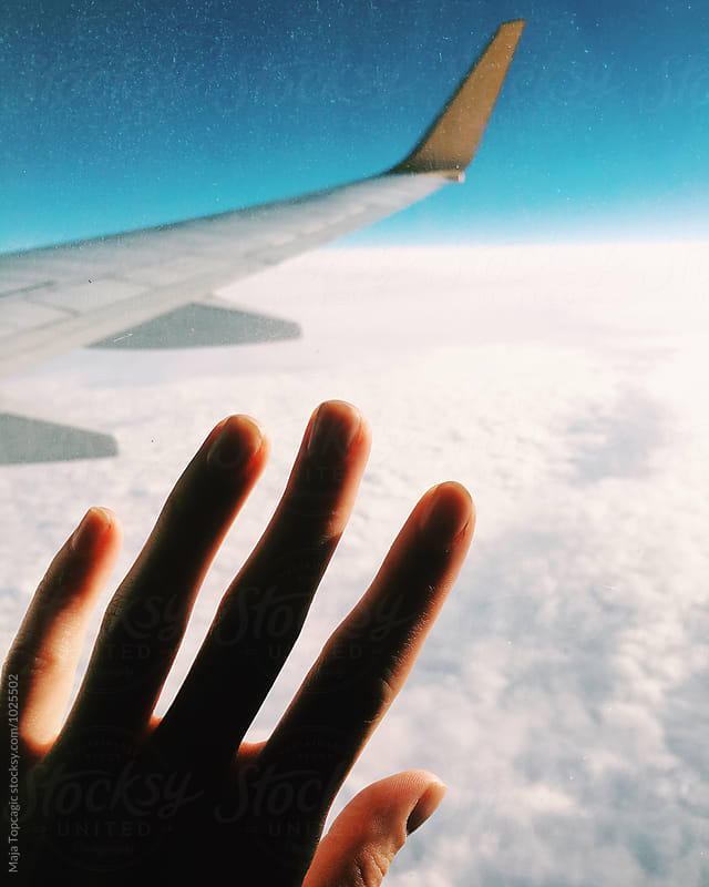 Female hand on an aeroplane window  by Maja Topcagic for Stocksy United