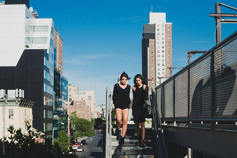 Friends walking with city in background by Lauren Naefe for Stocksy United