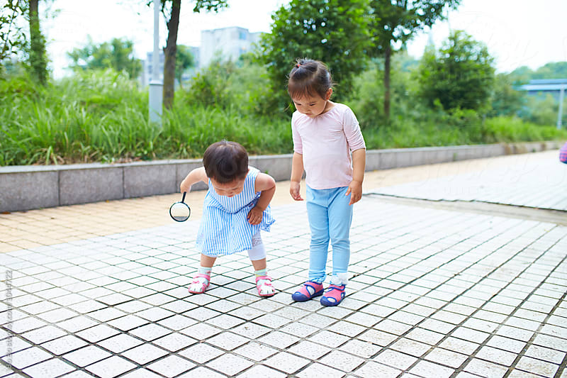 two little girl watching insect outdoor by cuiyan Liu for Stocksy United