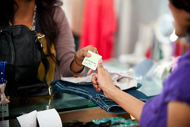 Boutique: Handing Credit Card to Cashier by Sean Locke for Stocksy United