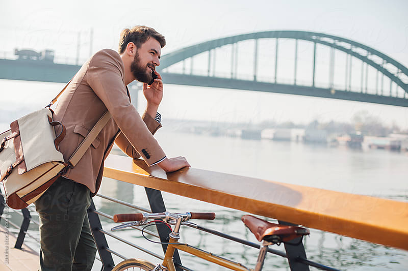 Man With Bike Telephoning by Lumina for Stocksy United