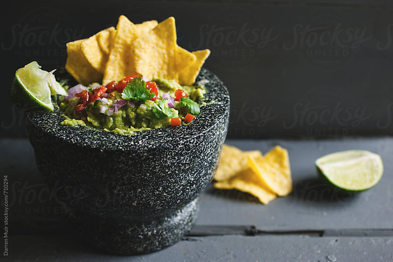 Guacamole and nacho chips on a table. by Darren Muir for Stocksy United
