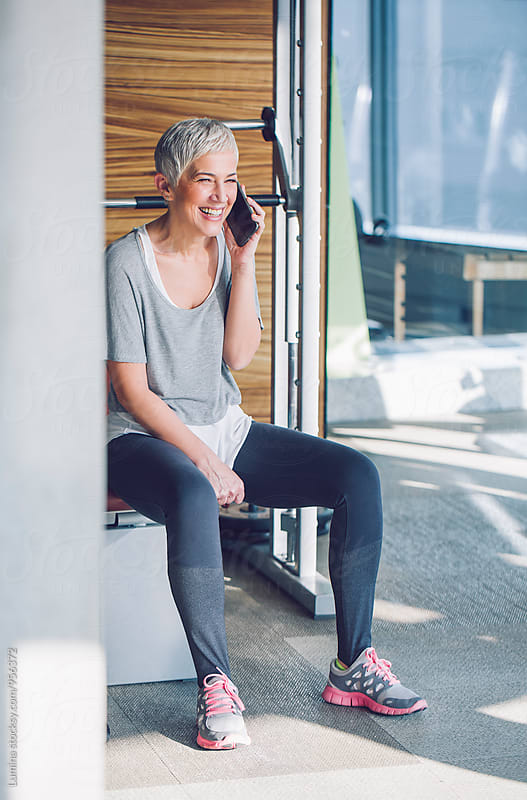 Woman Using a Mobile Phone in the Gym by Lumina for Stocksy United