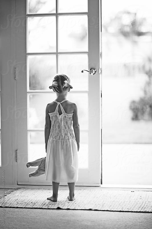 Girl In White Dress Holding Doll Facing French Door by Dina Giangregorio for Stocksy United