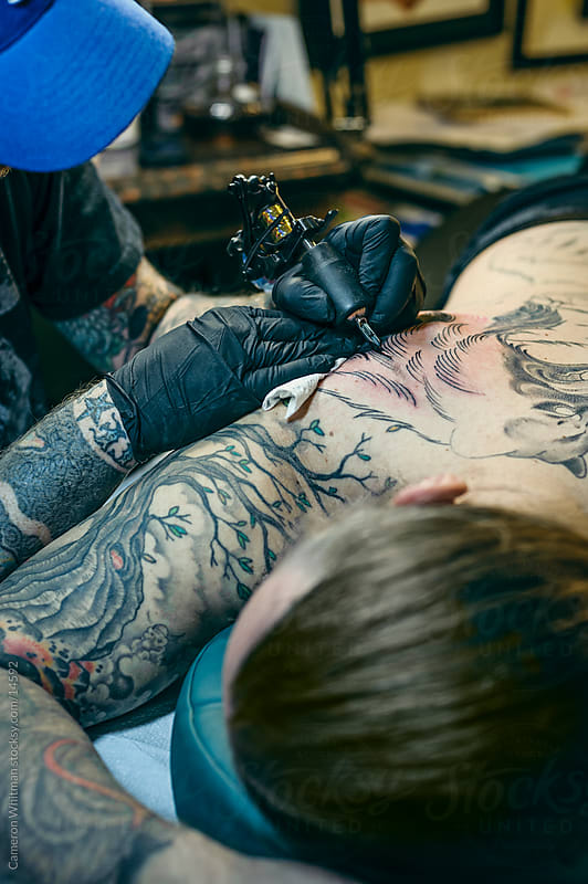 Tattoo Session: Shading in a back piece by Cameron Whitman for Stocksy United