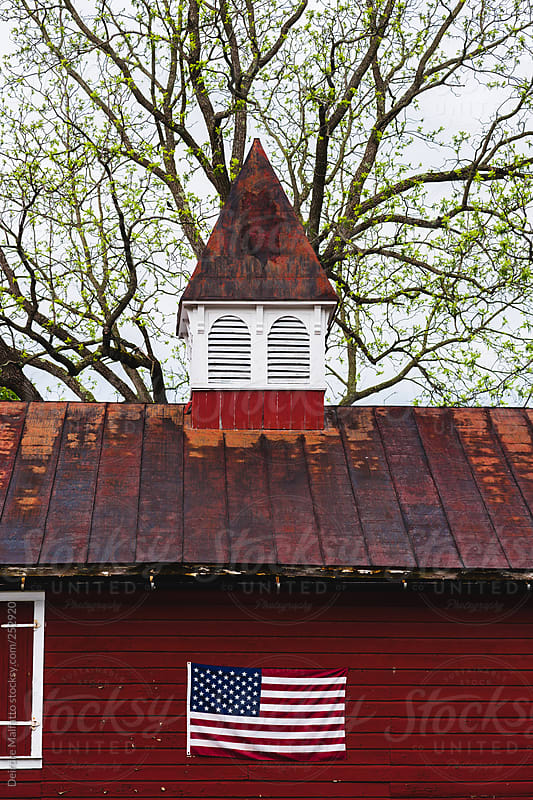 American Flag On Red Barn With Rusted Metal Roof By