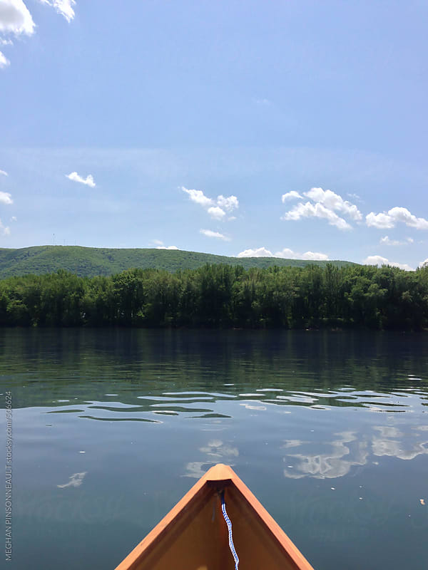 Canoe in Water with Blue Sky and Tree Line by MEGHAN PINSONNEAULT for Stocksy United