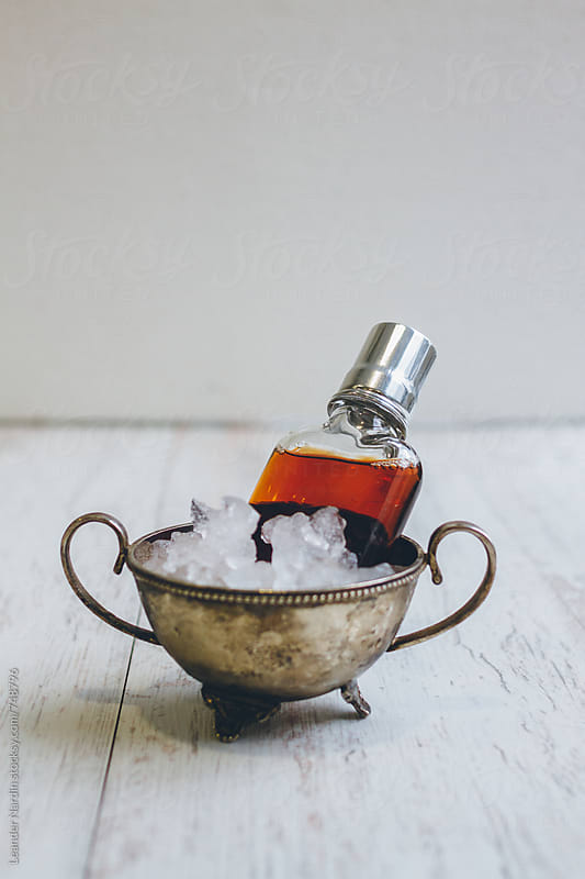 classic manhattan cocktail served in a flask on wooden white background by Leander Nardin for Stocksy United