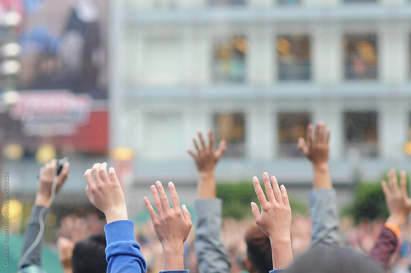A crowd of people in a city with their hands in the air by Chelsea Victoria for Stocksy United