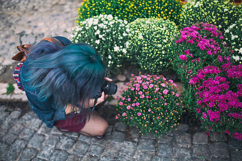 Beautiful young woman with blue hair taking photos of flowers in the city by Maja Topcagic for Stocksy United