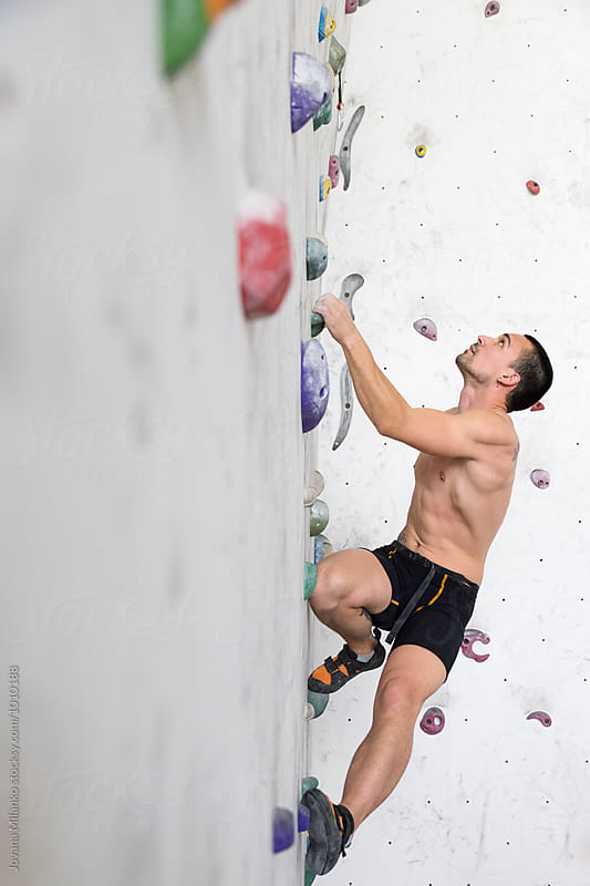 Free climber exercising on an indoor climbing wall by Jovana Milanko for Stocksy United