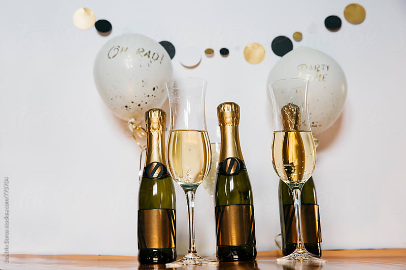 3 bottles of champagne, glasses with drink and party decor by Beatrix Boros for Stocksy United