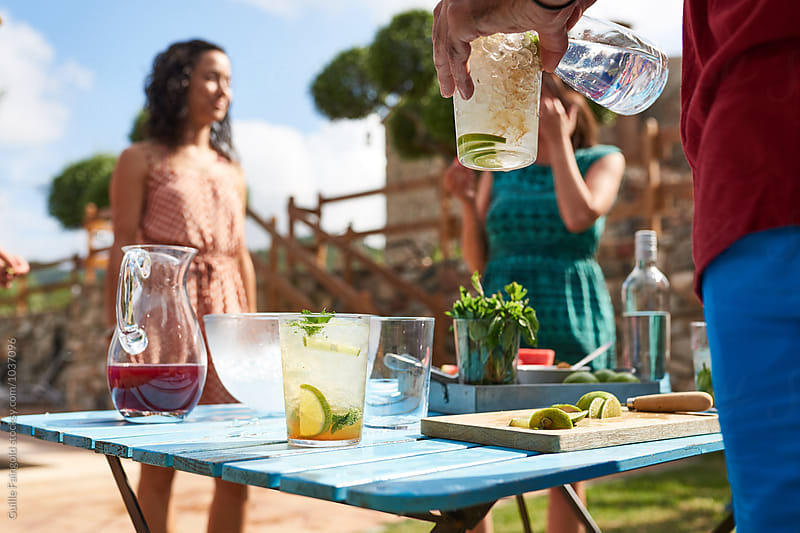 Barista pouring alcohol in mojito glass by Guille Faingold for Stocksy United