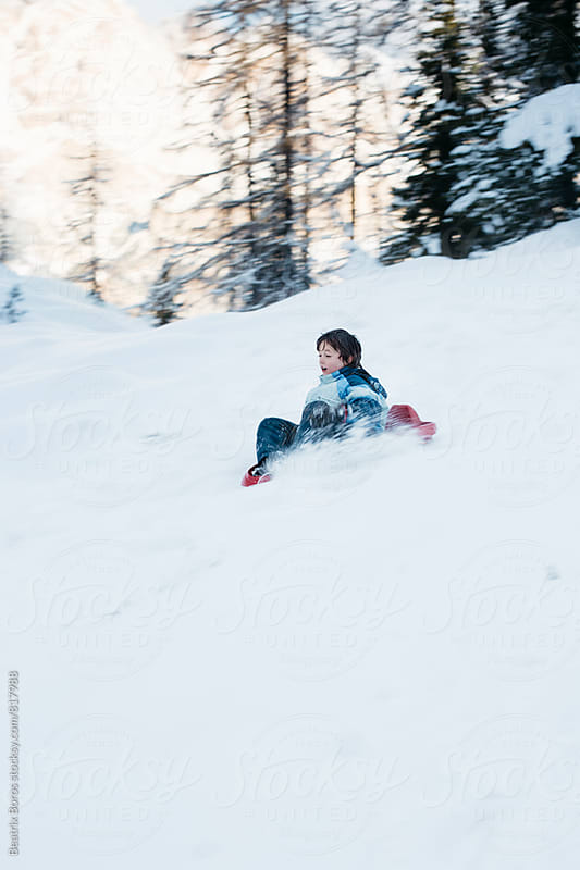 Boy going downhill on a sled with big copy space by Beatrix Boros for Stocksy United