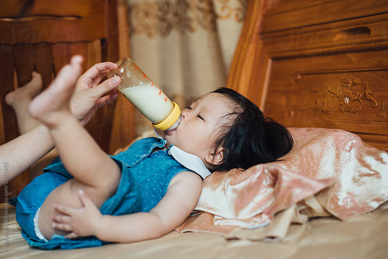 baby drinking milk by Xunbin Pan for Stocksy United