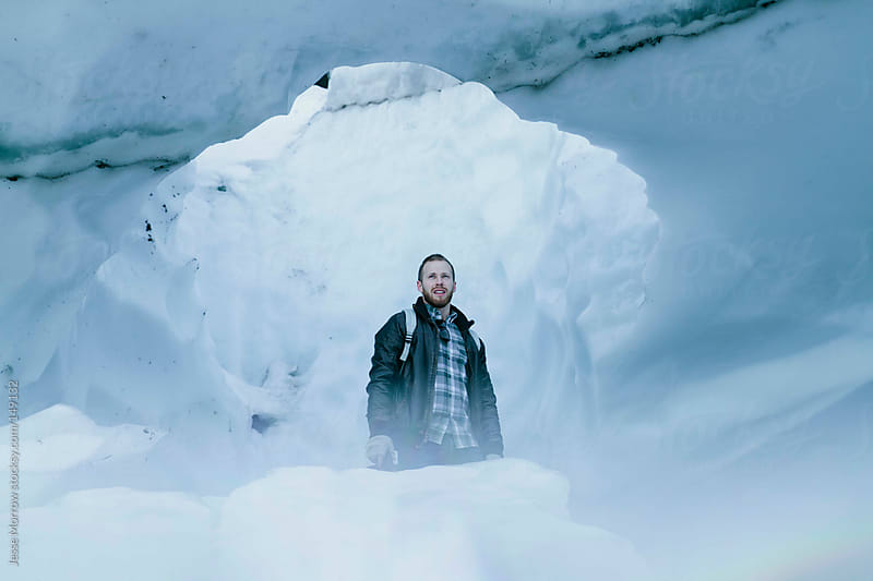 Young man stands outside Ice Cave by Jesse Morrow for Stocksy United