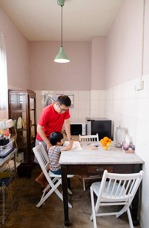 Dad helping young son with his homework by Alita Ong for Stocksy United